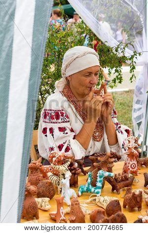 ADYGEA RUSSIA - AUGUST 19 2017: woman plays music on a clay whistle in the shop with clay Souvenirs and toys at the festival of cheese Adyghe in Adygea