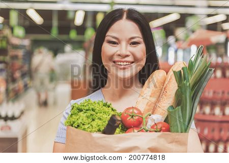 Glad woman is standing in supermarket and looking at camera with wide smile. She holding paper package full of goods. Portrait. Copy space on left side