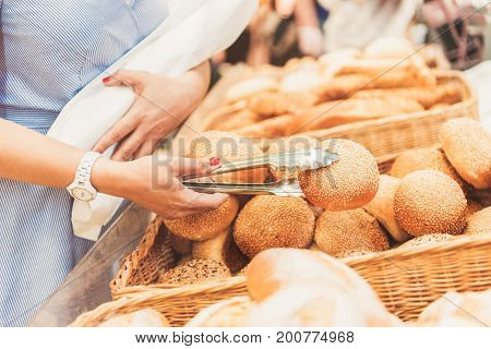 Woman is standing near basket full of bakery in supermarket and choosing palatable bun. Close up of female hand holding bread. Copy space on right side