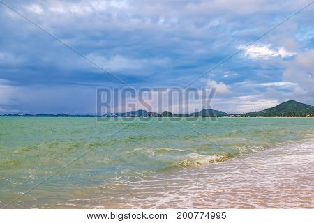 View of cloudy evening at Maenam beach, Koh Samui, Thailand. Beautiful seascape with foamy waves and protruding stones. Rainy ominous grey storm clouds - dramatic sky.