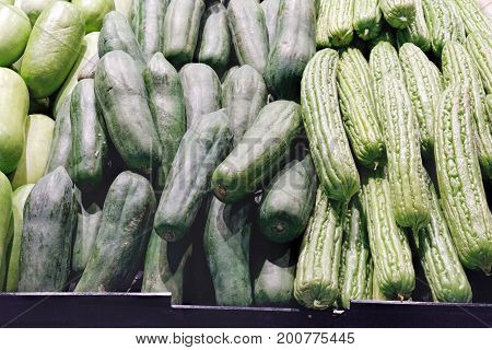 Pile of green zucchini summer squash for sale at the Thai night farmers market. Selective focus