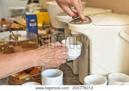 Woman pouring hot water for brewing a tea from thermo pot in hotel kitchen