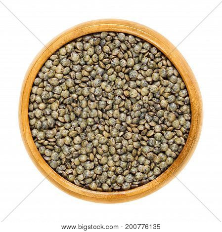Le Puy green lentils in wooden bowl. Dried small slate-gray seeds of Lens esculenta puyensis from Le Puy in Auvergne, France with unique peppery flavor. Macro food photo close up from above over white