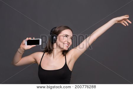 Favorite playlist. Woman enjoying music from mobile in earphones dancing on gray studio background