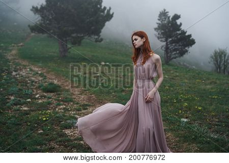 Beautiful young woman in a long dress in the mountains, fog.