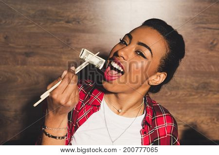 portrait of african american woman pretending eating money and looking at camera