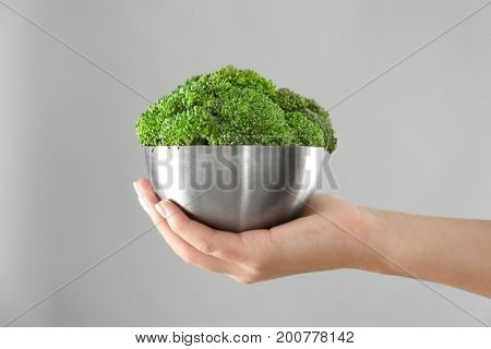 Hand holding metal bowl with fresh green broccoli