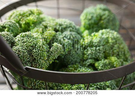 Green fresh broccoli in metal basket close-up