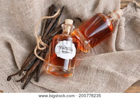 Bottles with aromatic extract and dry vanilla beans on napkin