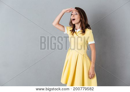 Pretty young girl in dress standing and looking far away with hand on her forehead isolated over gray background