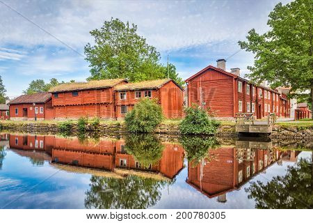 Old traditional red swedish wooden houses reflecting in Svartan river in Wadkoping historical quarter in Orebro Sweden