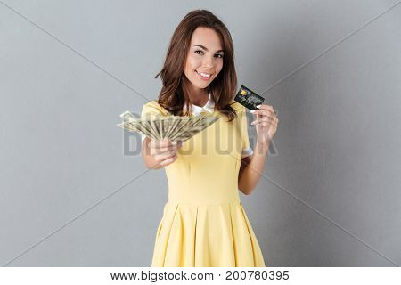 Image of cheerful young caucasian lady holding money and debit card in hands. Looking camera.