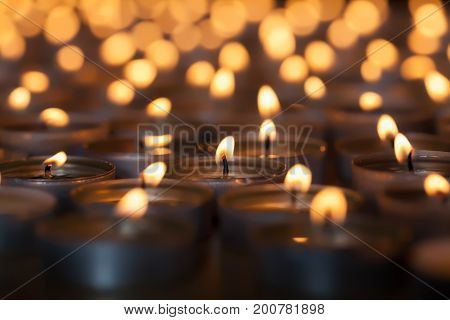 Lighted candle amongst hundreds of flaming tea light candles. Beautiful romantic candlelight. Selective focus on central lit wick.