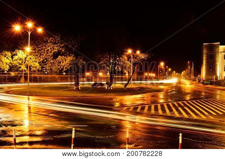Streets in the city at night lights and streaks of cars.