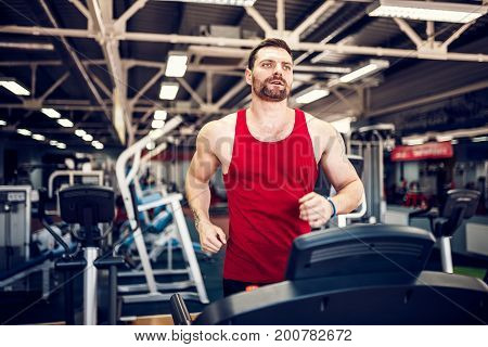 Fit Muscle Man Running on Treadmill in Gym.