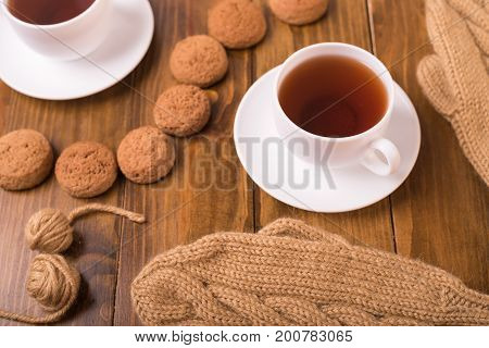 Cup of coffee, a pair of beige woolen mittens and seven oat cookie on a wooden table