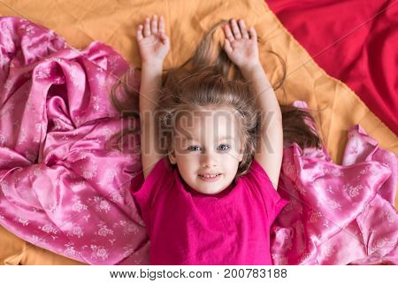 Little girl lying on a pile of multicoloured fabric. Shot overhead with a soft focus and natural light.