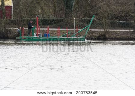 HEILIGENHAUS NRW GERMANY - MARCH 03 2017: Special ship working platform in use on a small pond. Wet dredging at the Abtskuecher Teich in Heiligenhaus.