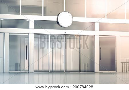 Blank white round signage mockup on the store glass sliding doors entrance 3d rendering. Commercial building automatic entry banner mock up. Closed transparent business centre facade front view.