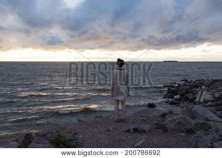 one 1 girl woman standing back on the rocks on the sea shore the waves splash on the sunset sky with purple clouds Gulf of Finland