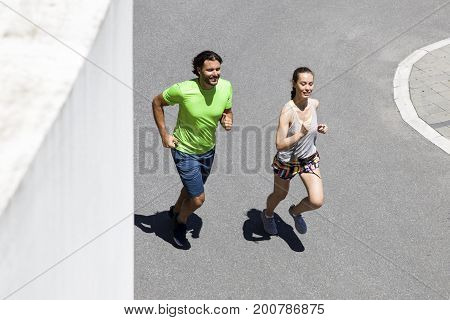 Handsome Man And Beautiful Woman Jogging Together On Street