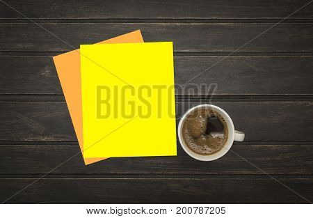 Blank letterhead and coffee cup on vintage wooden table background. Blank branding template. Mock up for branding identity for placing your design. Top view.