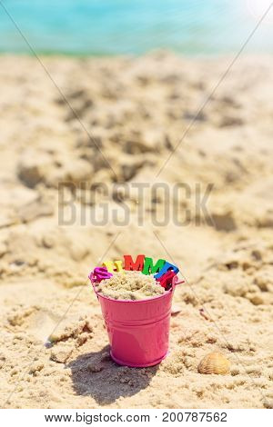 Baby pink metal bucket by the sea in the rays of a bright sun summer day