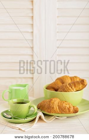 Coffee with milk and croissants on a light wooden background. Selective focus.