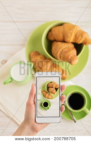 Female hand holding smart phone with picture of coffee with croissants. Selective focus.