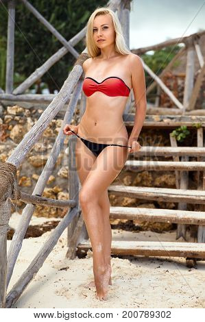 Beautiful blonde woman in the red bikini posing on the lonely beach near wooden stair. Zanzibar. Nungwi.