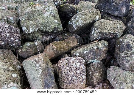 Abstract background and texture of old stone pile in the ground.