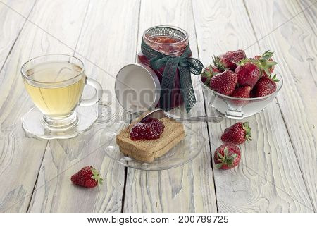 Strawberry jam, rusks and tea in a cup on a wooden table close-up