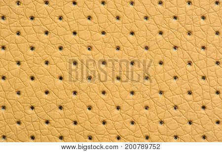 Yellow perforated artificial leather texture as a background