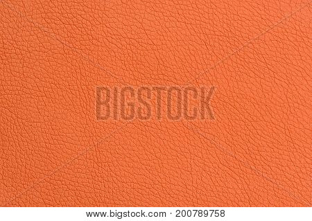 A close-up of orange artificial leather background texture