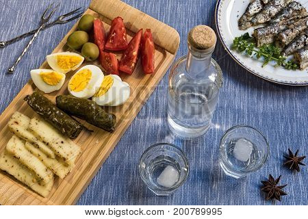 Glasses and bottle of traditional drink Ouzo or Raki and appetizers