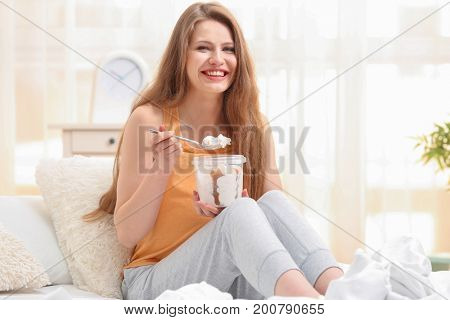 Emotional pregnant woman eating ice-cream in light room. Pregnancy hormones concept