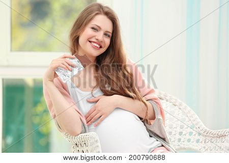Emotional pregnant woman sitting in arm chair and eating chocolate. Pregnancy hormones concept