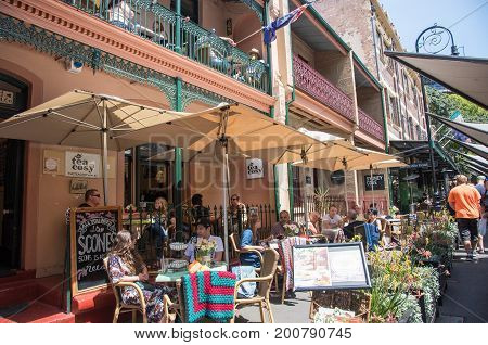 SYDNEY,NSW,AUSTRALIA-NOVEMBER 20,2016: The Tea Cosy sidewalk cafe with people and handmade blankets in The Rocks district of Sydney, Australia.