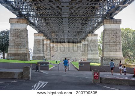 SYDNEY,NSW,AUSTRALIA-NOVEMBER 20,2016: Tourists under the Sydney Harbour Bridge with granite pylons, Australian flag and cannon in Sydney, Australia.