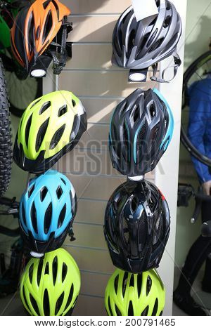 Stand with new modern bicycle helmets in shop