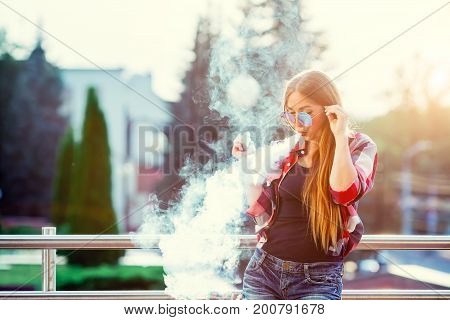 Young pretty hipster woman vaping and releases a cloud of vapor. The evening sunset over the city.