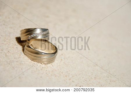 Wedding rings on sand in the sun