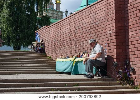 SERGIEV POSAD/ RUSSIA - AUGUST 3, 2017. The seller of Russian nesting dolls in front of the Sergiev Posad monastery (The Trinity Lavra of St. Sergius). Moscow region, Russia.