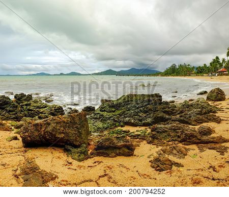 View of cloudy evening at Maenam beach, Koh Samui, Thailand. Beautiful seascape with sea and protruding stones. Rainy ominous grey storm clouds - dramatic sky.