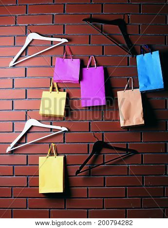 colorful paper shopping bag or package as holiday present or gift and wood plastic fashion hanger or rack from wardrobe on brown textured brick wall background copy space