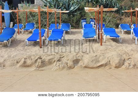 Beach lounge bed with umbrella to protect people from sun, on white sand beach. Tropical holiday banner background with empty copyspace. Travel, vacation, relax, tourism, sun bathing, tanning concept