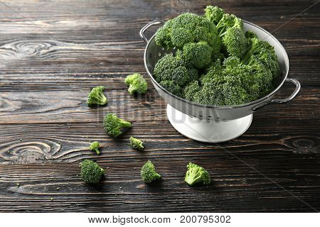 Fresh green broccoli in colander on brown wooden table