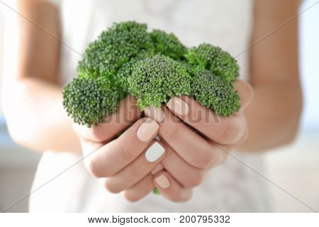 Fresh green broccoli in hands close-up