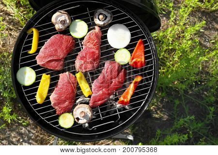 Raw tasty beefsteaks and vegetables cooking on barbecue grill outdoors