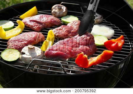 Raw tasty beefsteaks and vegetables cooking on barbecue grill, close up